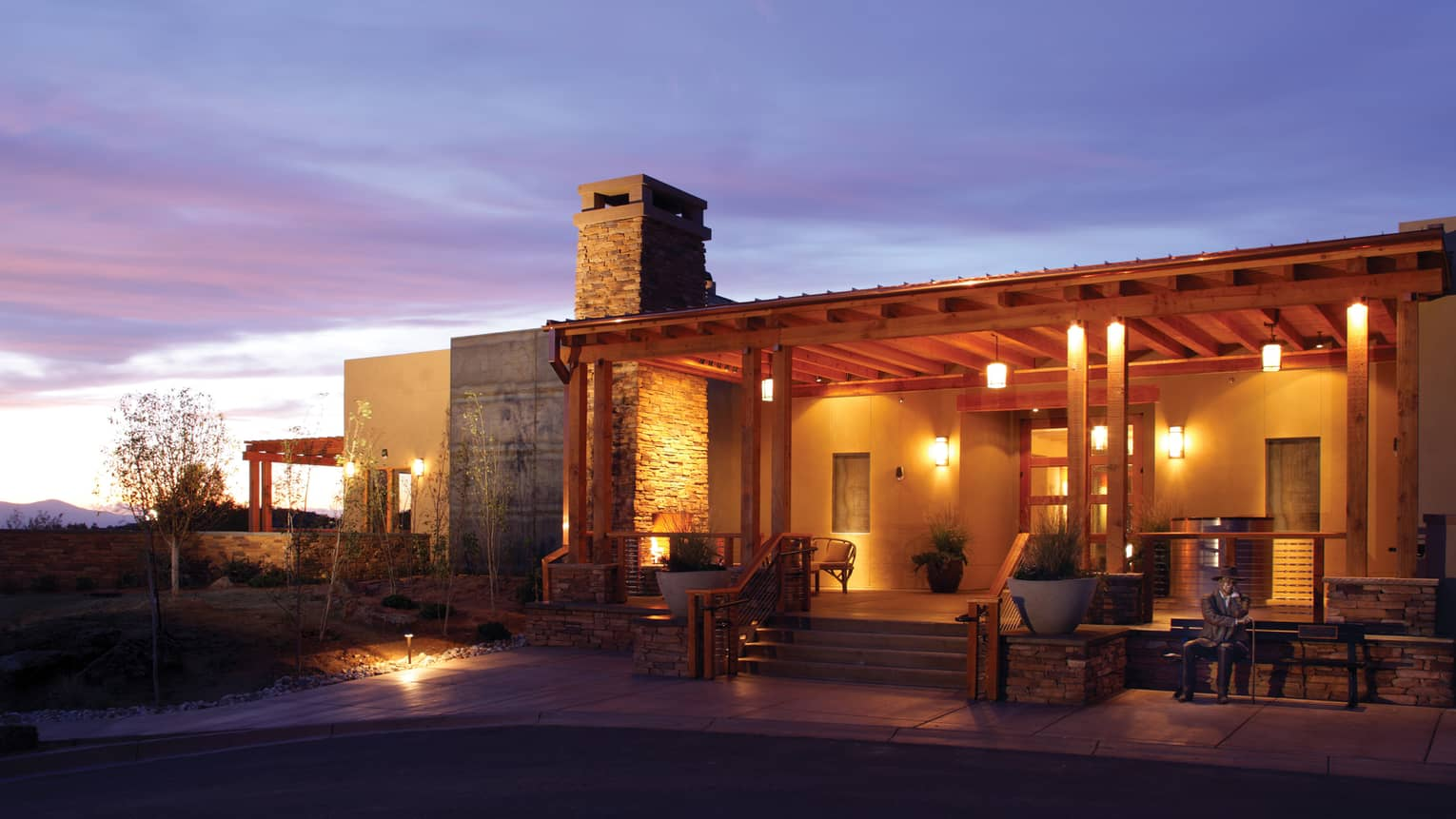 Stone exterior of Four Seasons Resort Rancho Encantado Santa Fe with lights at night