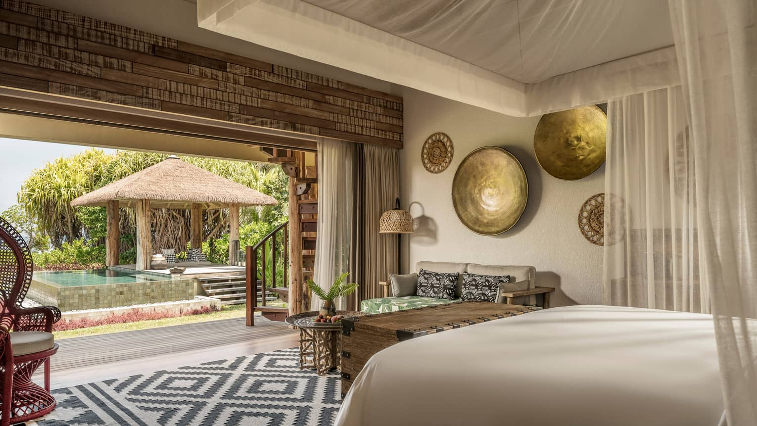 Luxury villa with canopy over bed, artwork on wall, rattan chair opens up to pool