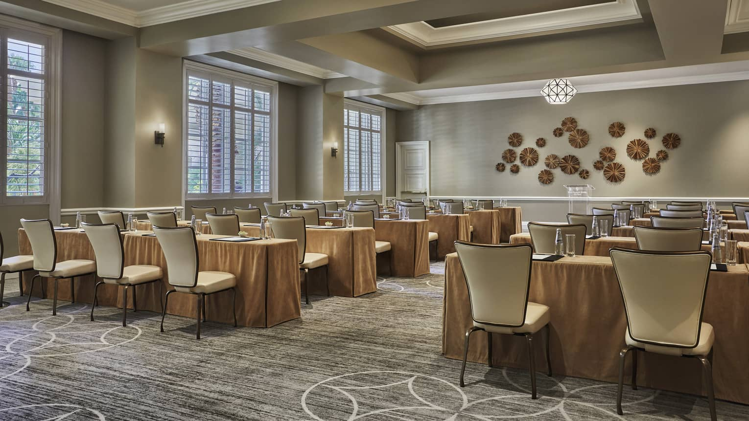 Palm Room conference, rows of meeting tables and chairs facing decorative wall
