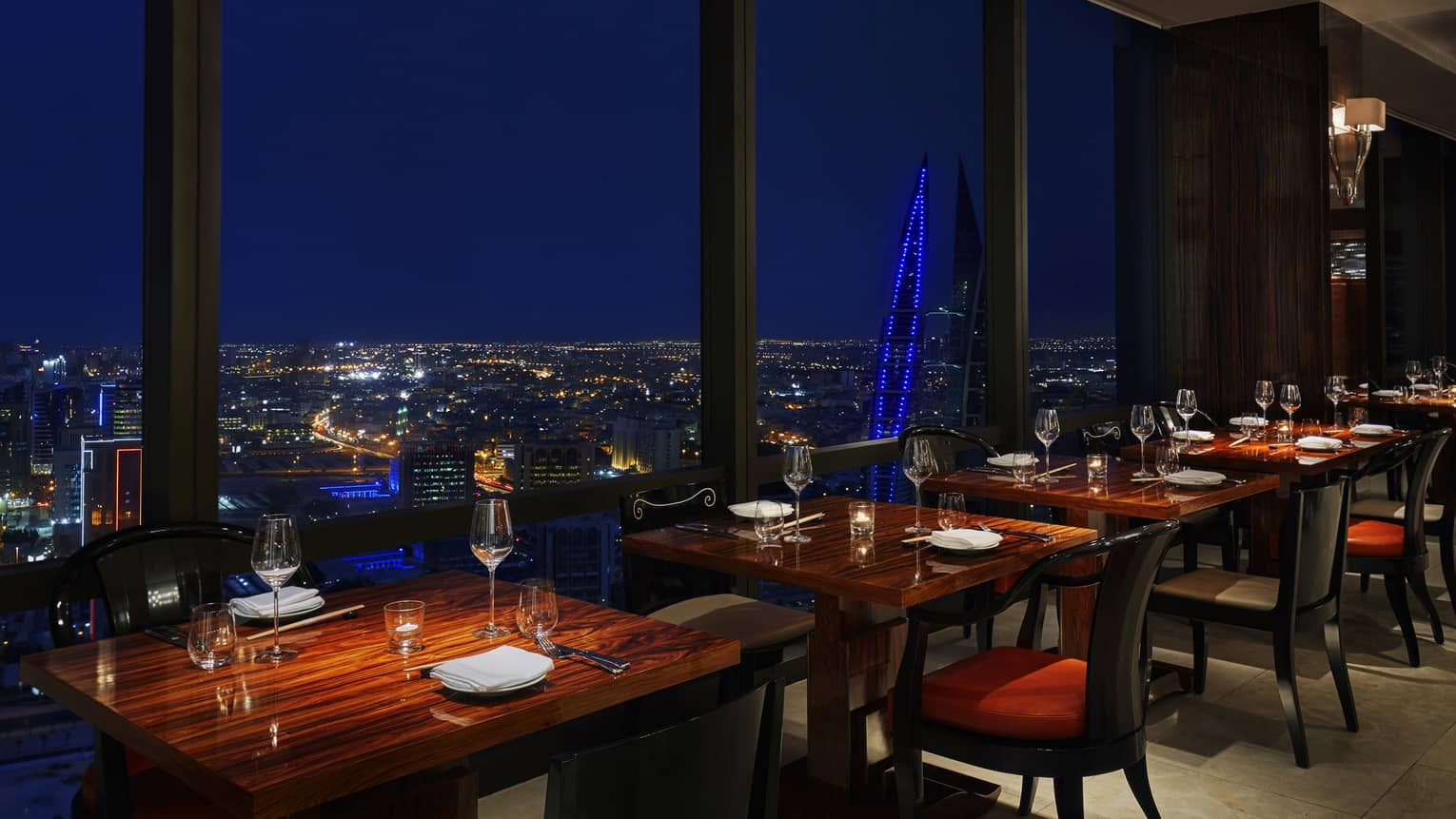Re Asian Cuisine dining tables along floor-to-ceiling windows looking out at city lights at night