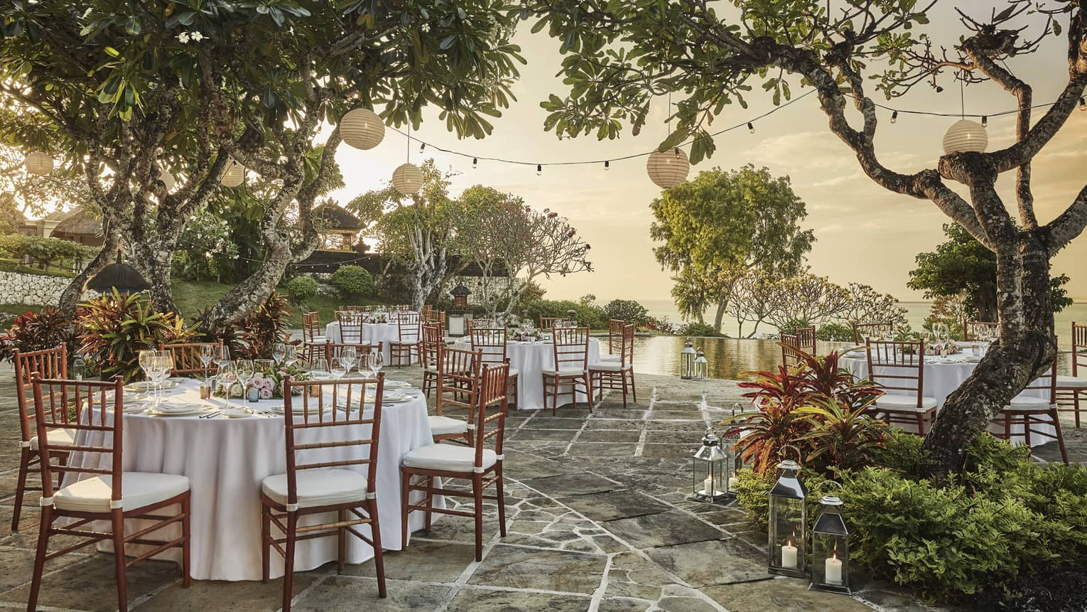 Patio wedding reception at sunset, small round banquet tables and chairs under trees