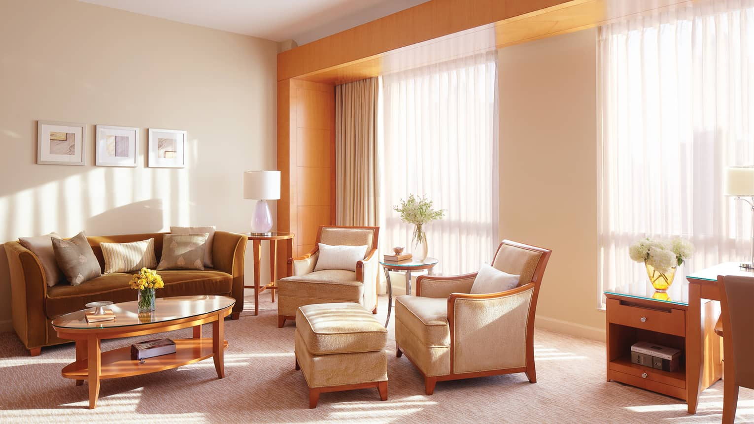 Executive Suite beige velvet armchairs, bronze sofa, table by large windows, sheer curtains