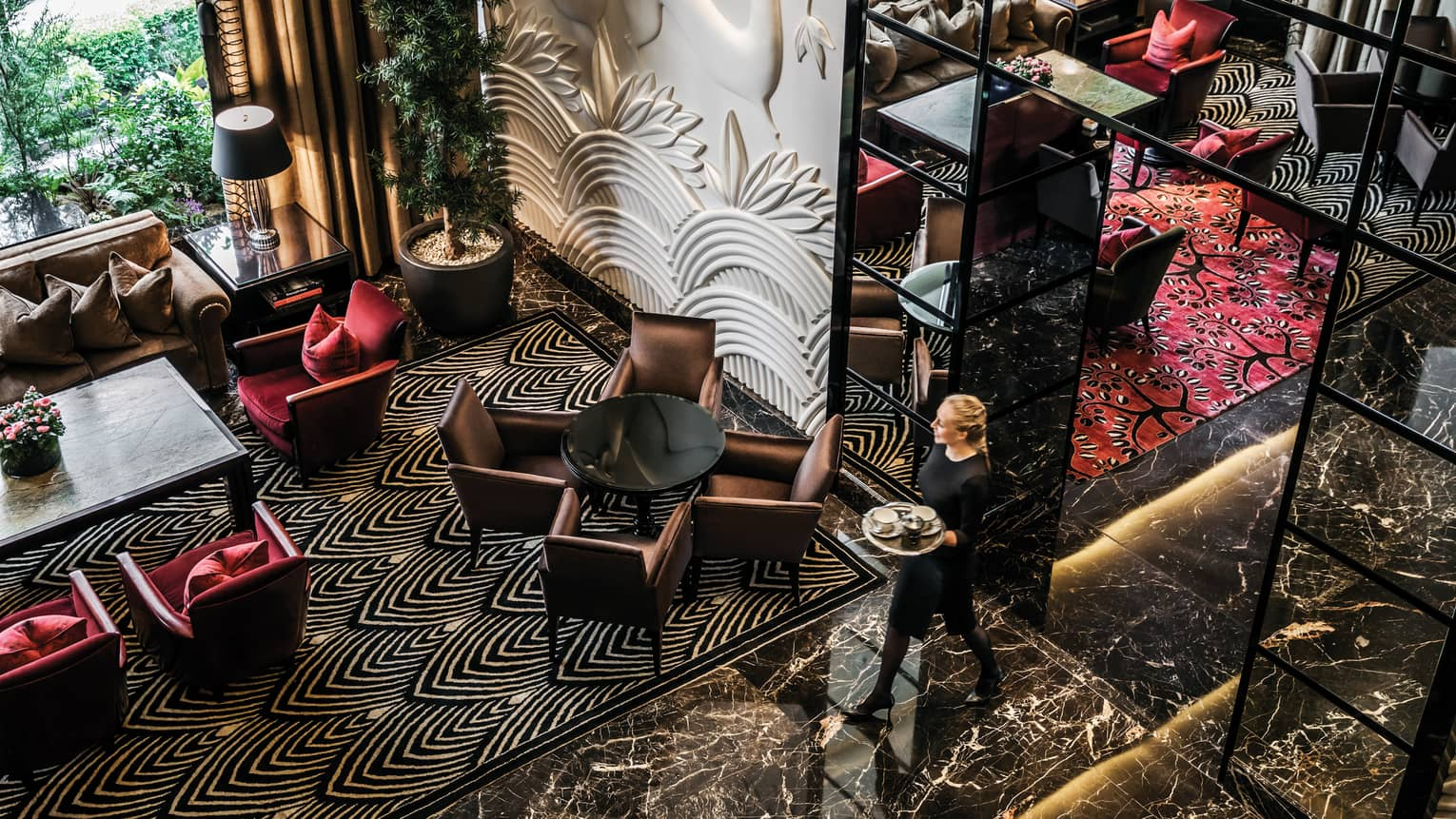Aerial view of server carrying tray through Amaranto Lounge, black marble floors, white accent walls