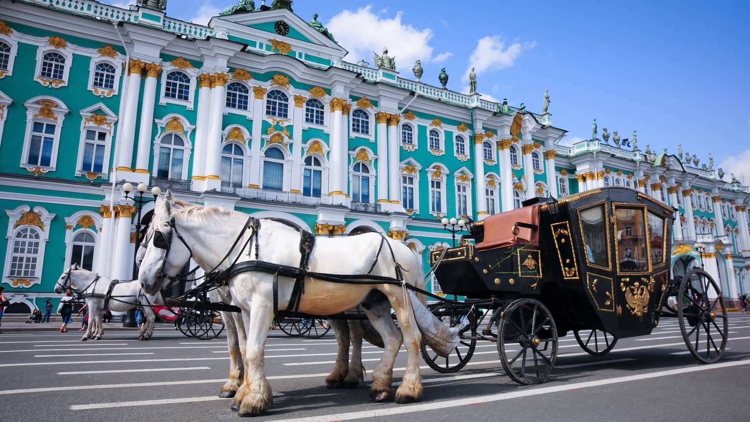 White horse tied to black-and-gold buggy waits outside the green Hermitage Museum