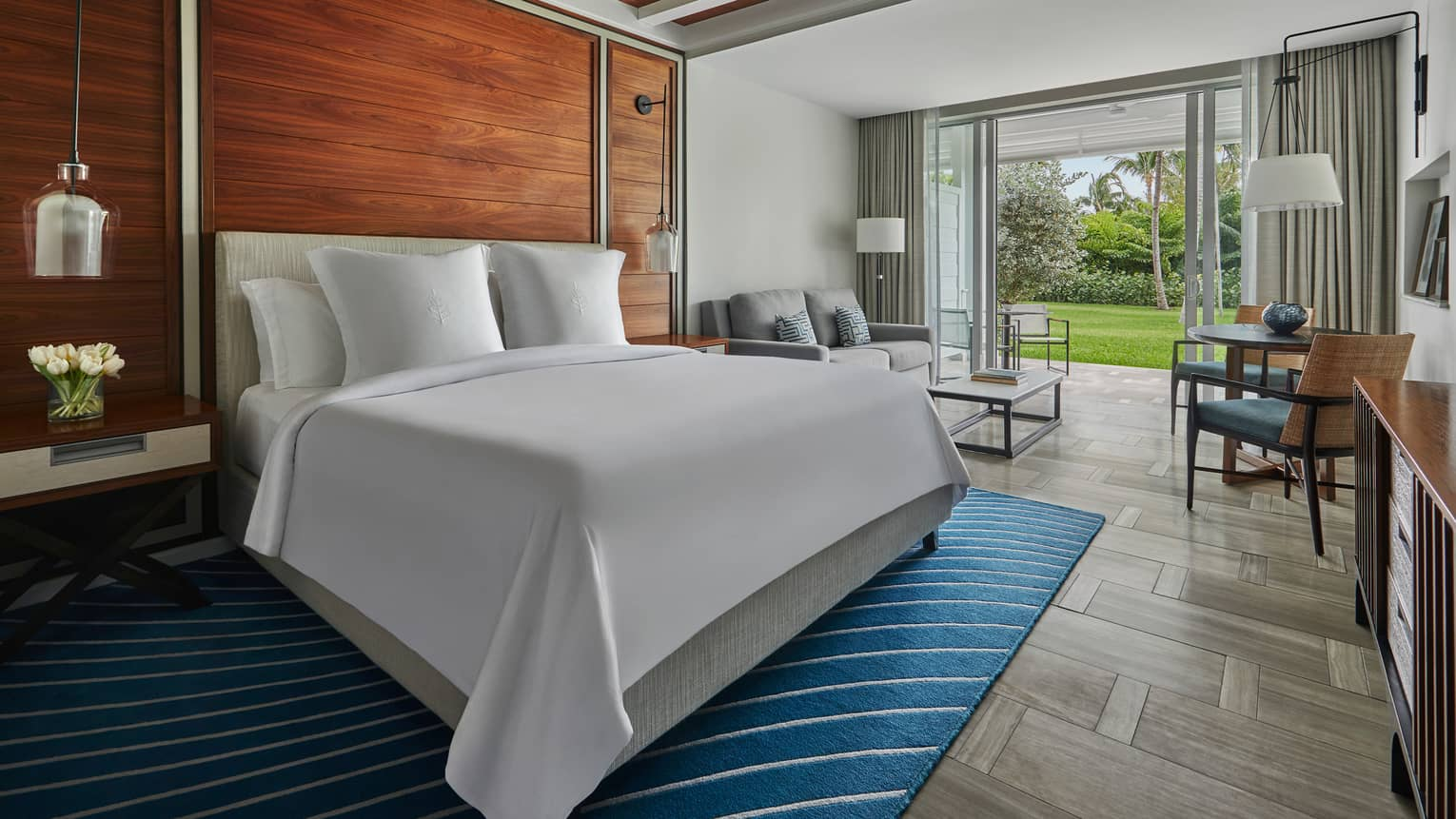 Garden-View Room bed against wood accent wall, seating area by open glass doors to patio