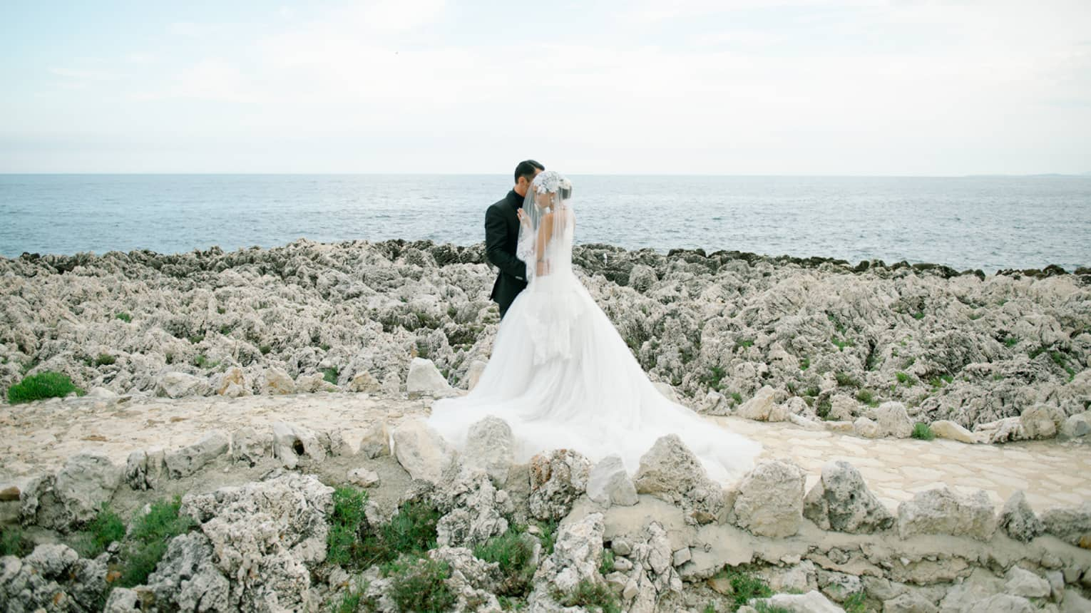 Groom and bride wearing veil over face in embrace, standing on rocky beach at sparkling blue sea