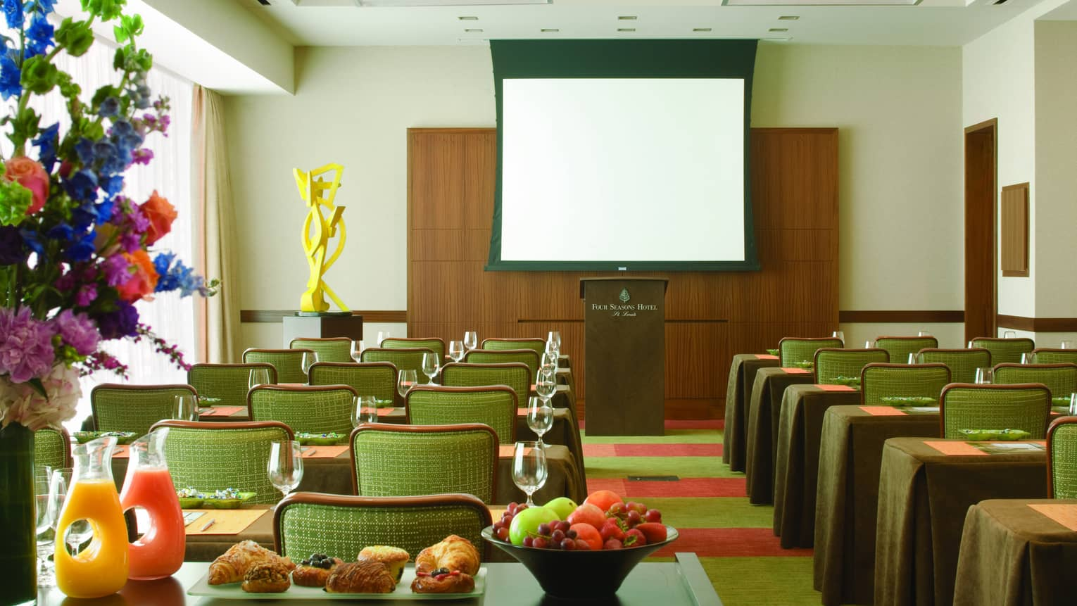 Gateway Meeting Room, rows of small meeting tables face podium, breakfast station