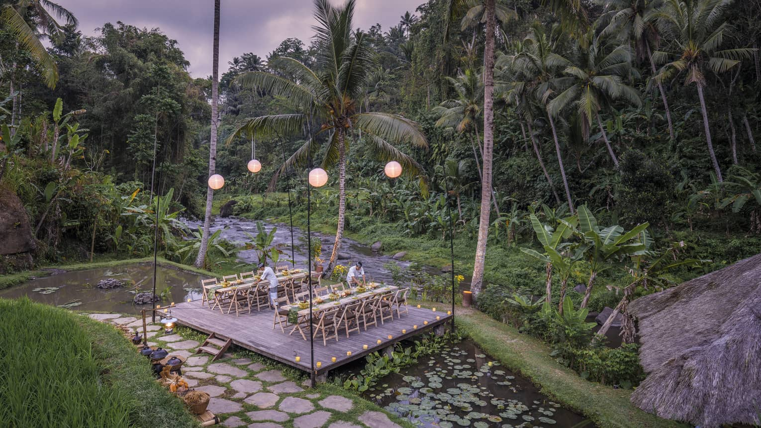 Megibung Dinner is set on a wooden deck as the sun sets beyond lush trees