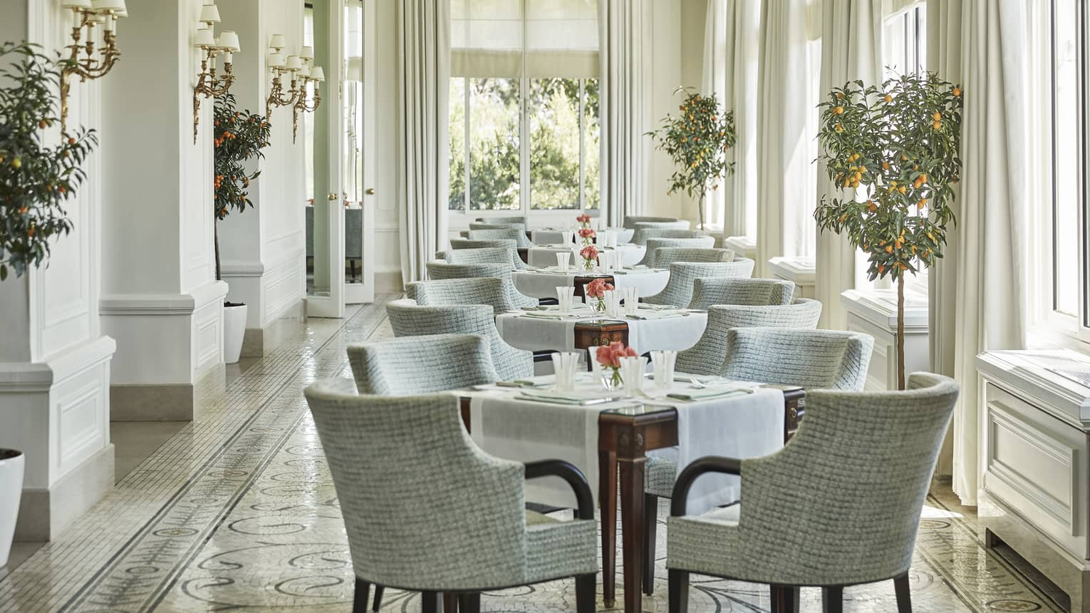 Grey chairs around tables in sunny Le Veranda dining room