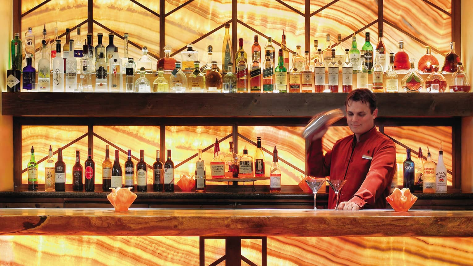Bartender in red jacket with cocktail shaker in front of two martini glasses on bar with illuminated wood grain