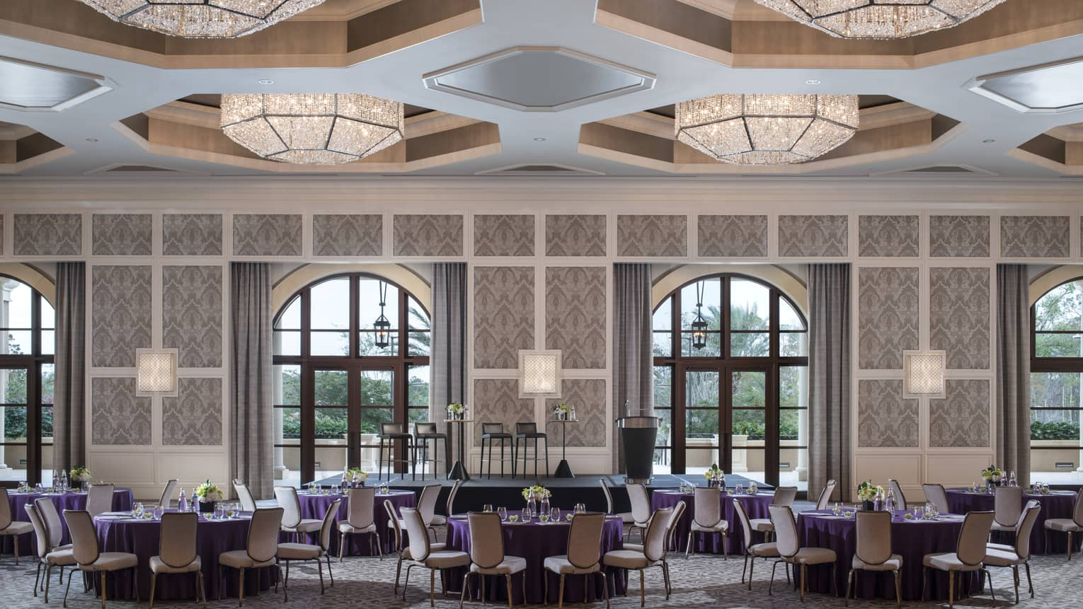 A ballroom at four seasons resort orlando at walt disney world is ready for guests with circular tables covered in purple table cloths