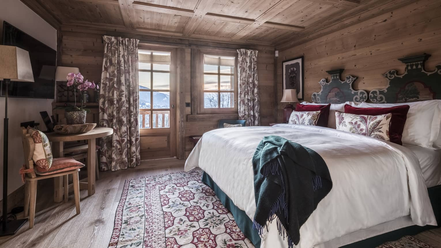 Spacious Gentiane Room bed, chairs and patio door to balcony with Megève valley views