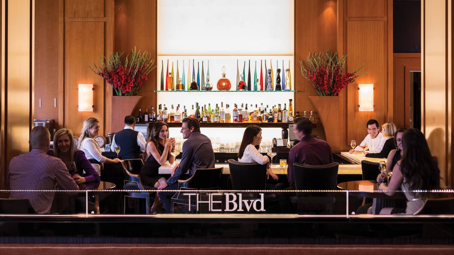 Guests socialize at lounge tables, bar behind The Blvd sign on railing
