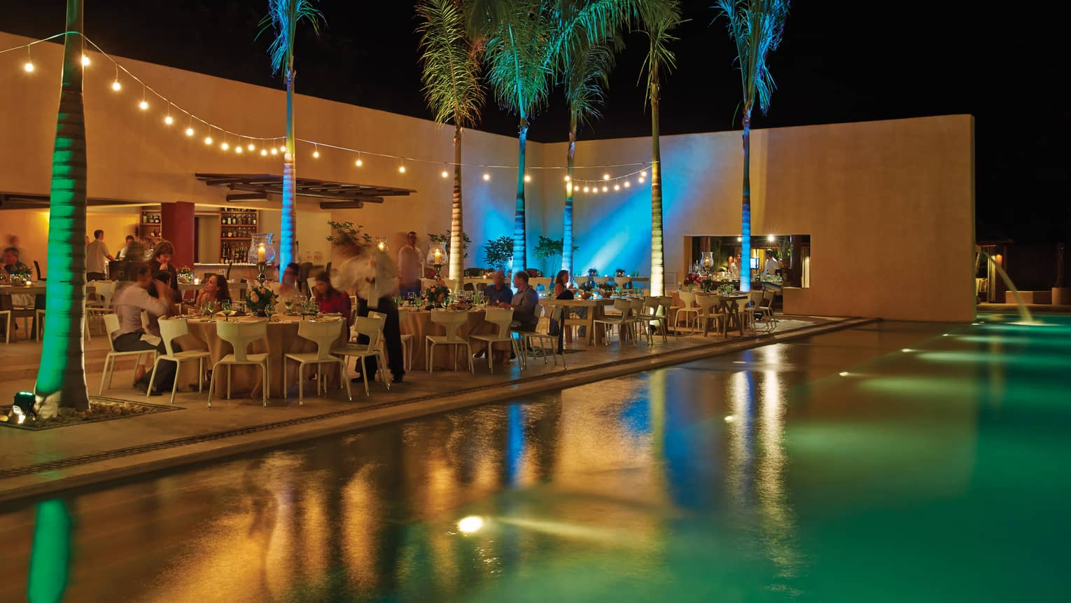 Banquet, colourful lights and palm trees along modern Tamai swimming pool at night