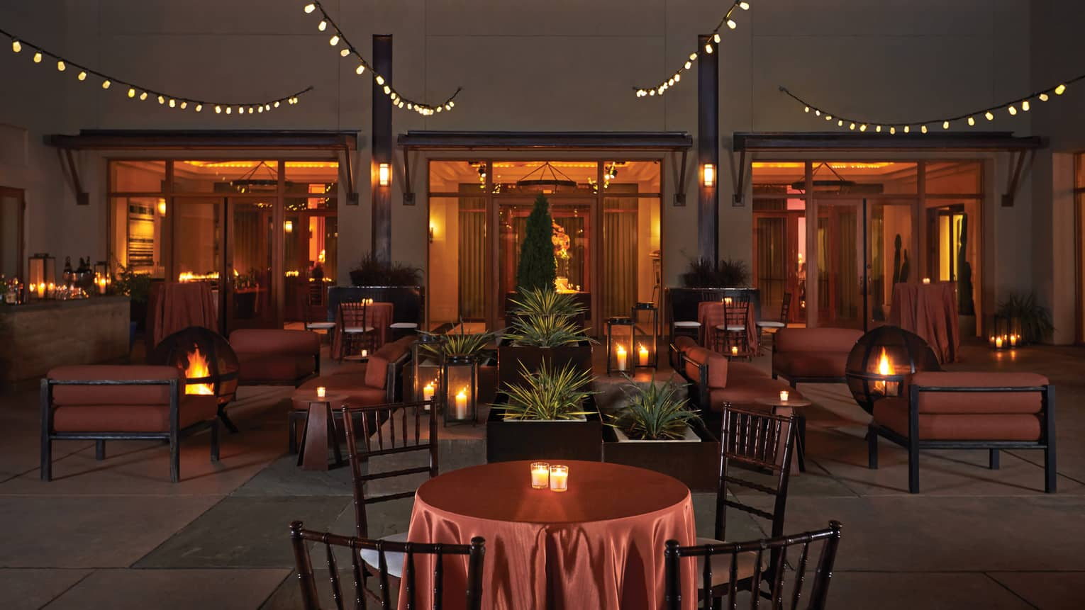 Terra courtyard at night, lounge furniture surrounding fire pits, candles, strings of lights