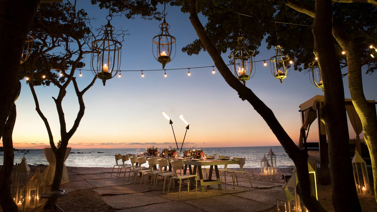 Lanterns hang from trees near private dining table with torches on beach at sunset
