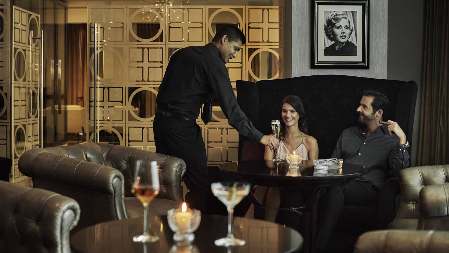 Zsa Zsa lounge staff places glass of Champagne on table in front of smiling couple