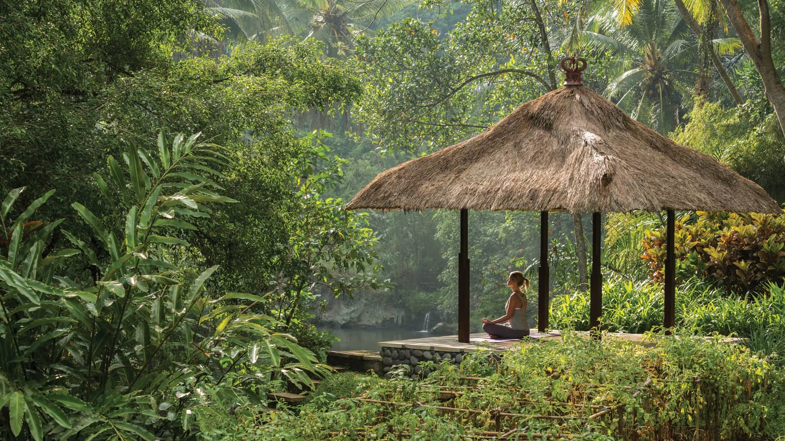 Woman meditating on pavilion hut by the Ayung River in Bali