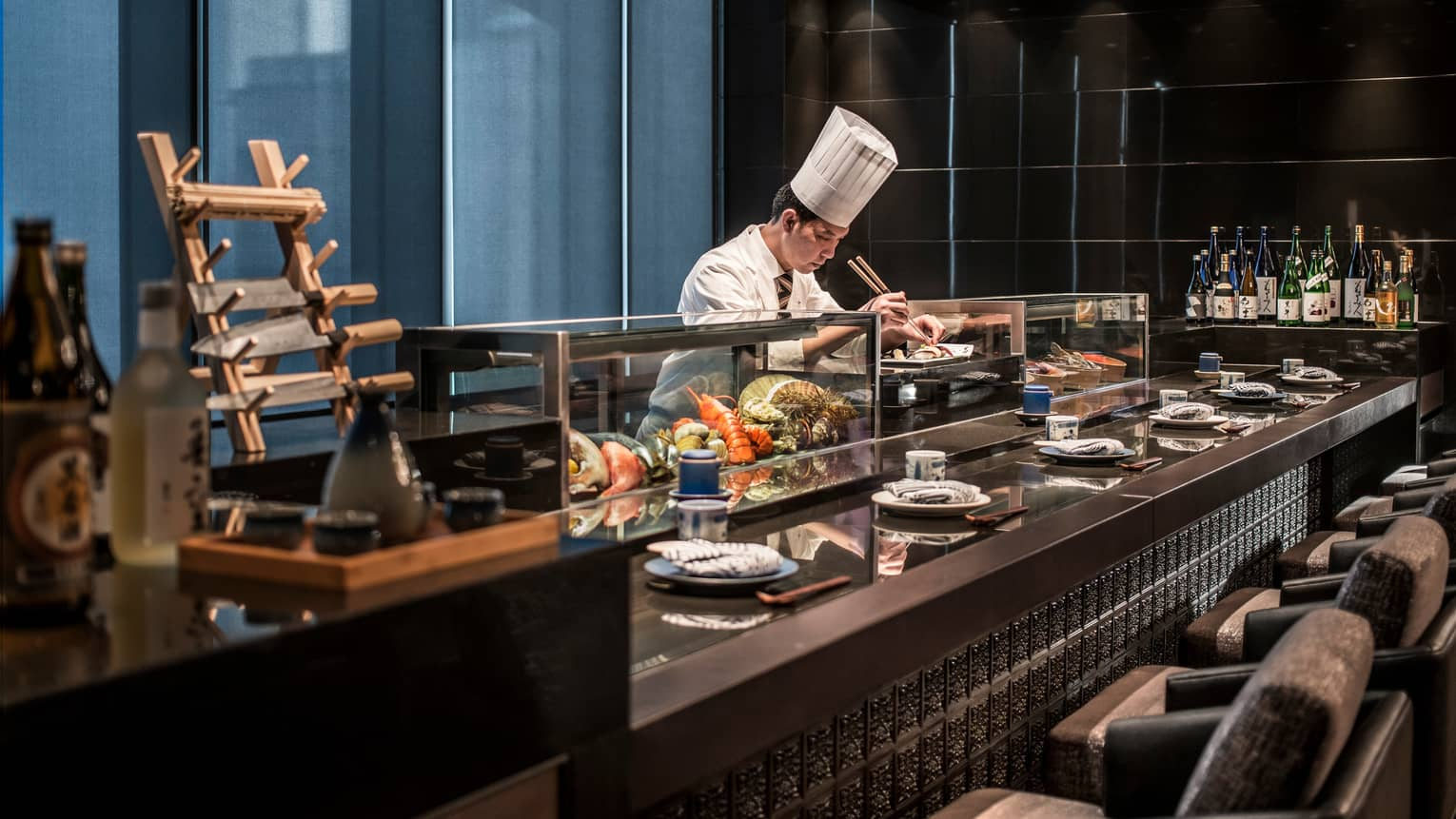 Kawa chef in tall white hat sets fresh sushi on plate by glass display with lobsters, fish