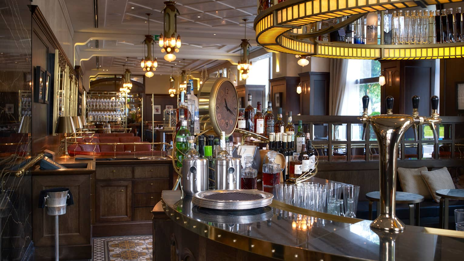 KOLLÁZS Brasserie & Bar curved wood bar with round light overhead, large clock, wine bottles