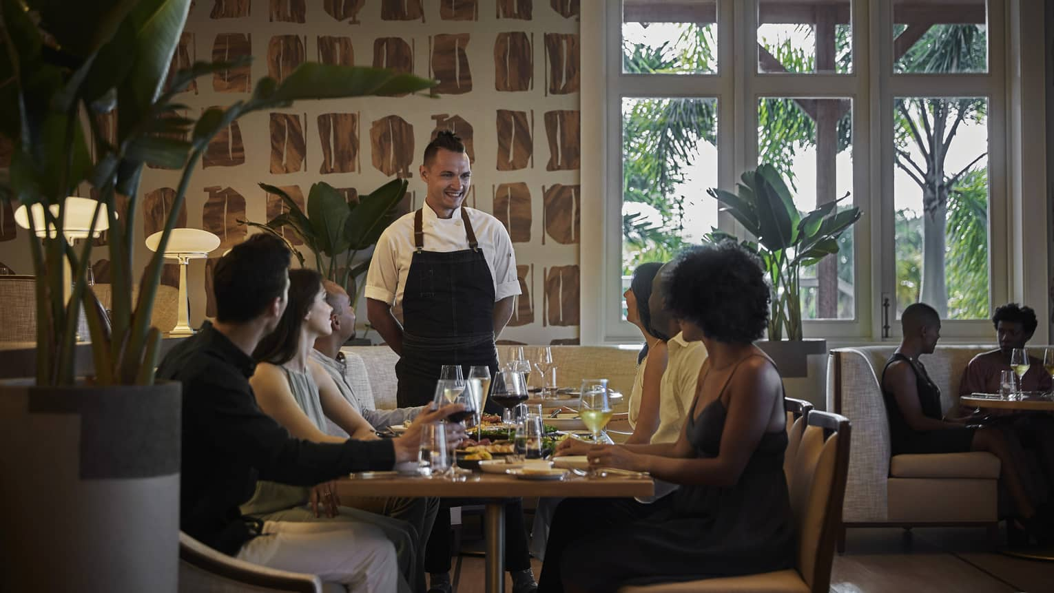A chef talks to a table of four people inside restaurant, windows look out to trees