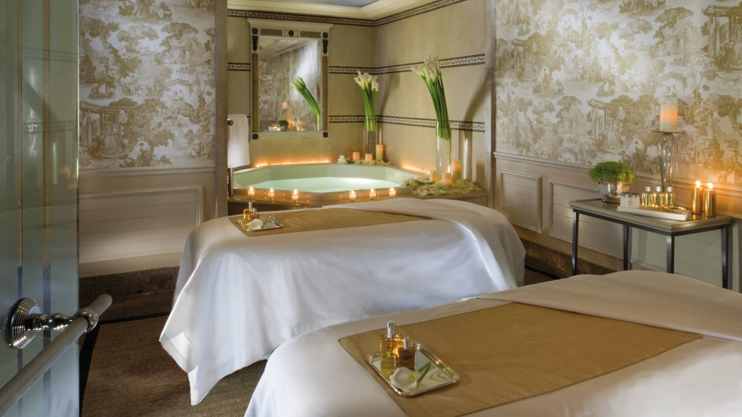 Couples massage beds with spa trays by tub lined with candles