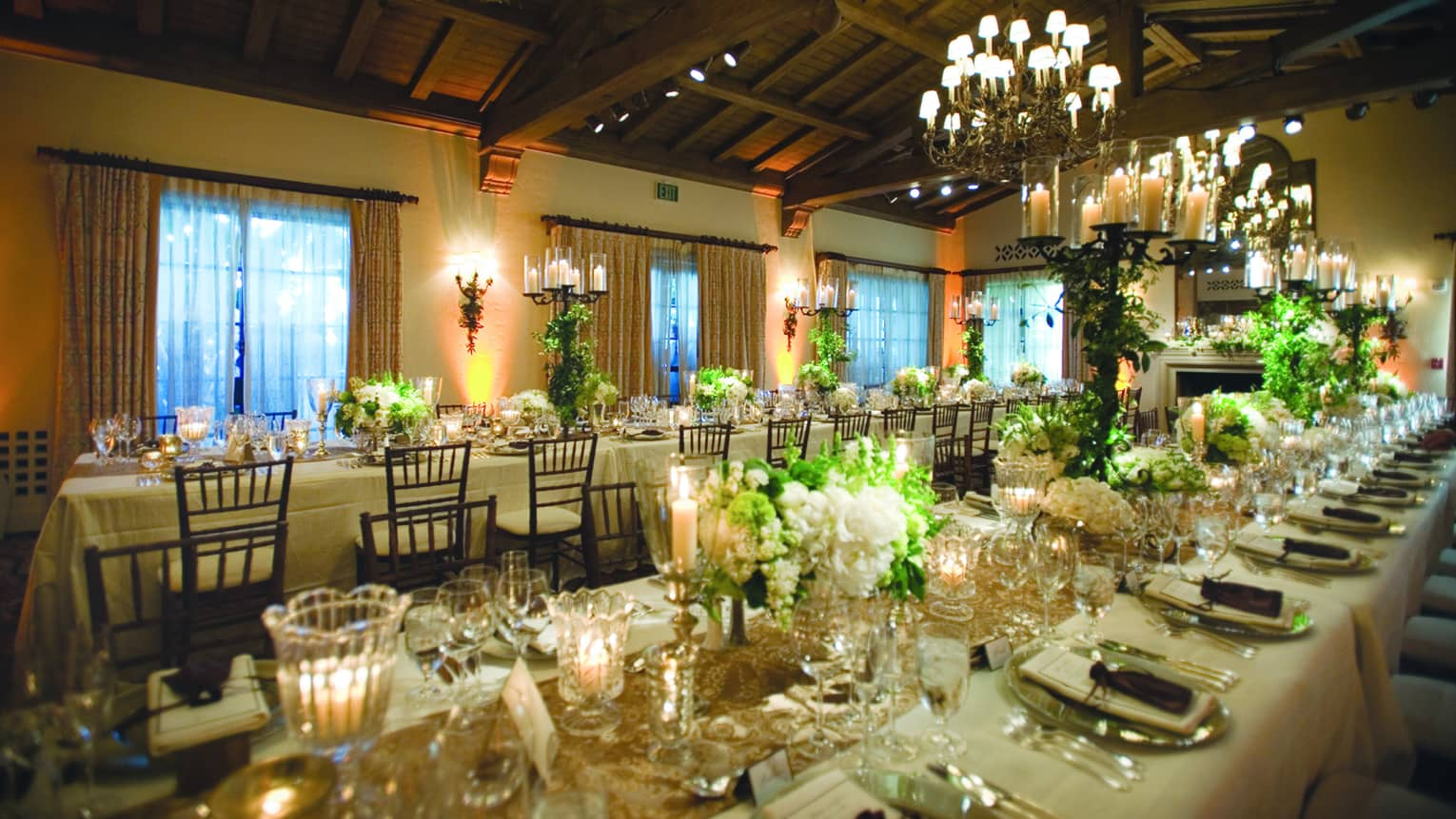 Long wedding banquet tables with glowing candles, white flowers