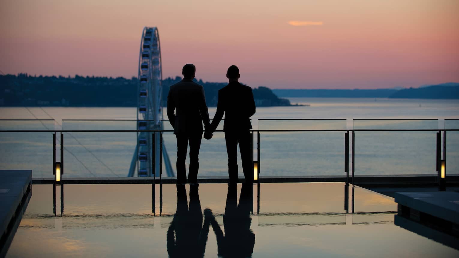 Silhouette of couple wearing suits and holding hands, looking over ocean at sunset