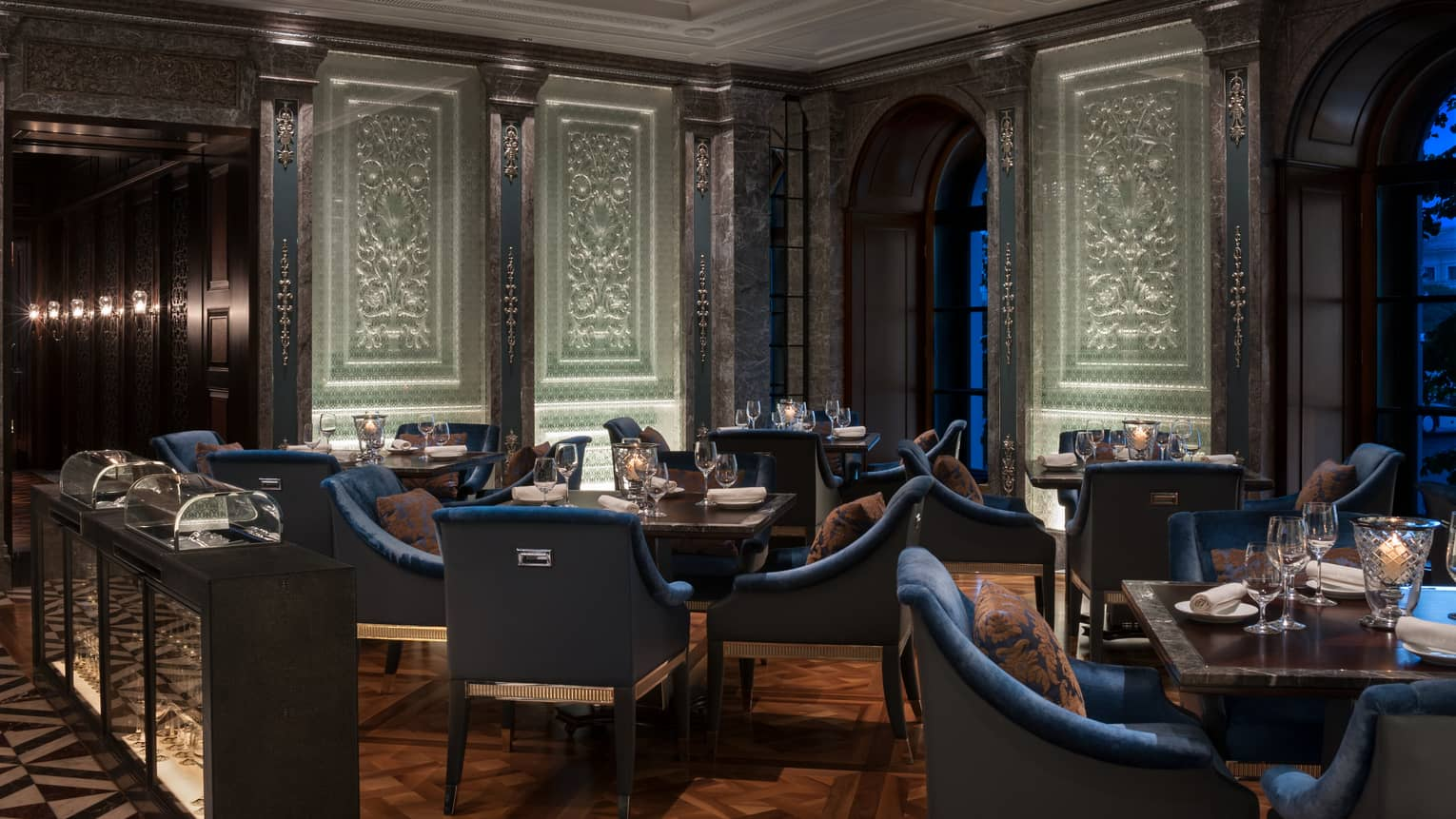 Percorso dining room blue velvet chairs, tables under tall white panels with carved details