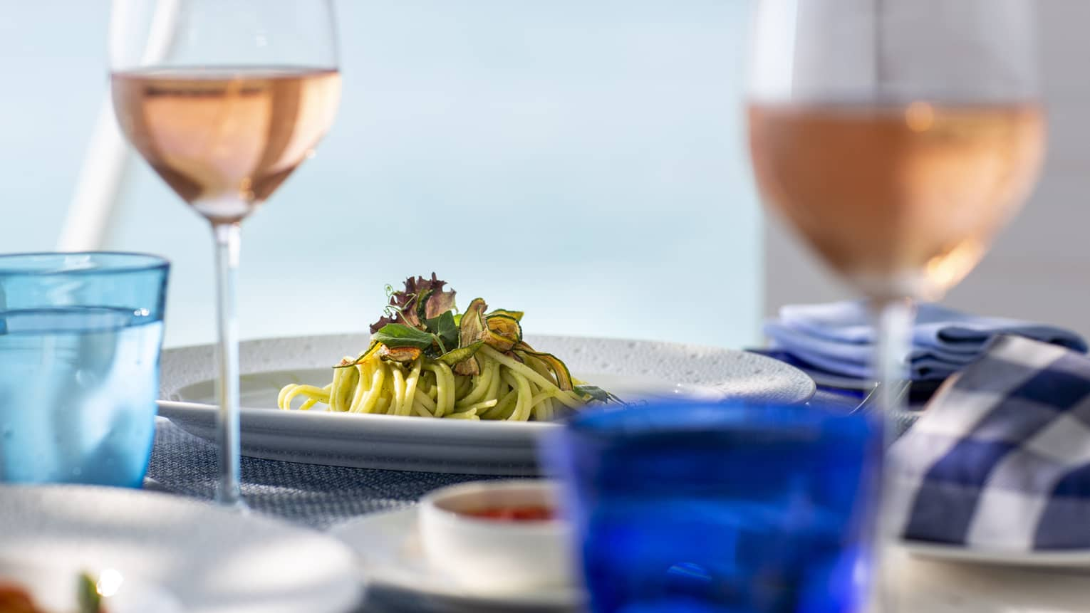 A side view of a table with glasses of rose and a pasta dish over looking the ocean in Four Seasons Maldives - Landaa