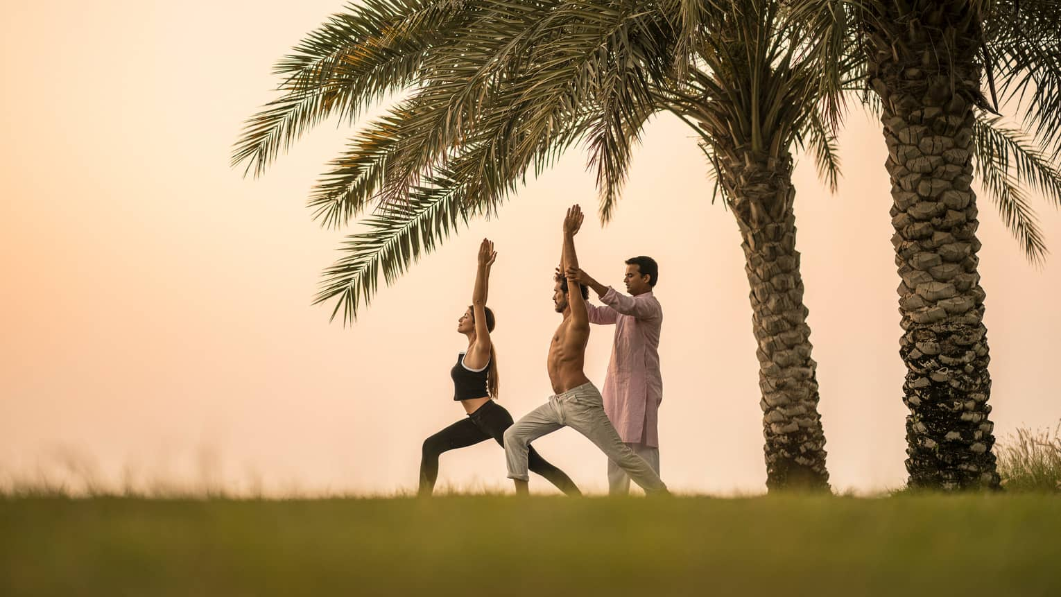 Yogi assists man in yoga stretch next to woman on lawn in front of two palm trees at sunrise