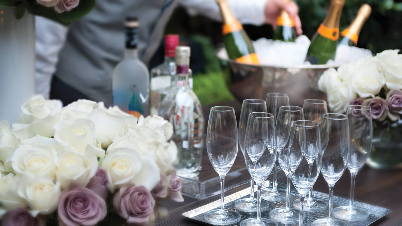 Close-up of white and purple roses, empty Champagne glasses on tray in front of ice bucket, bottles