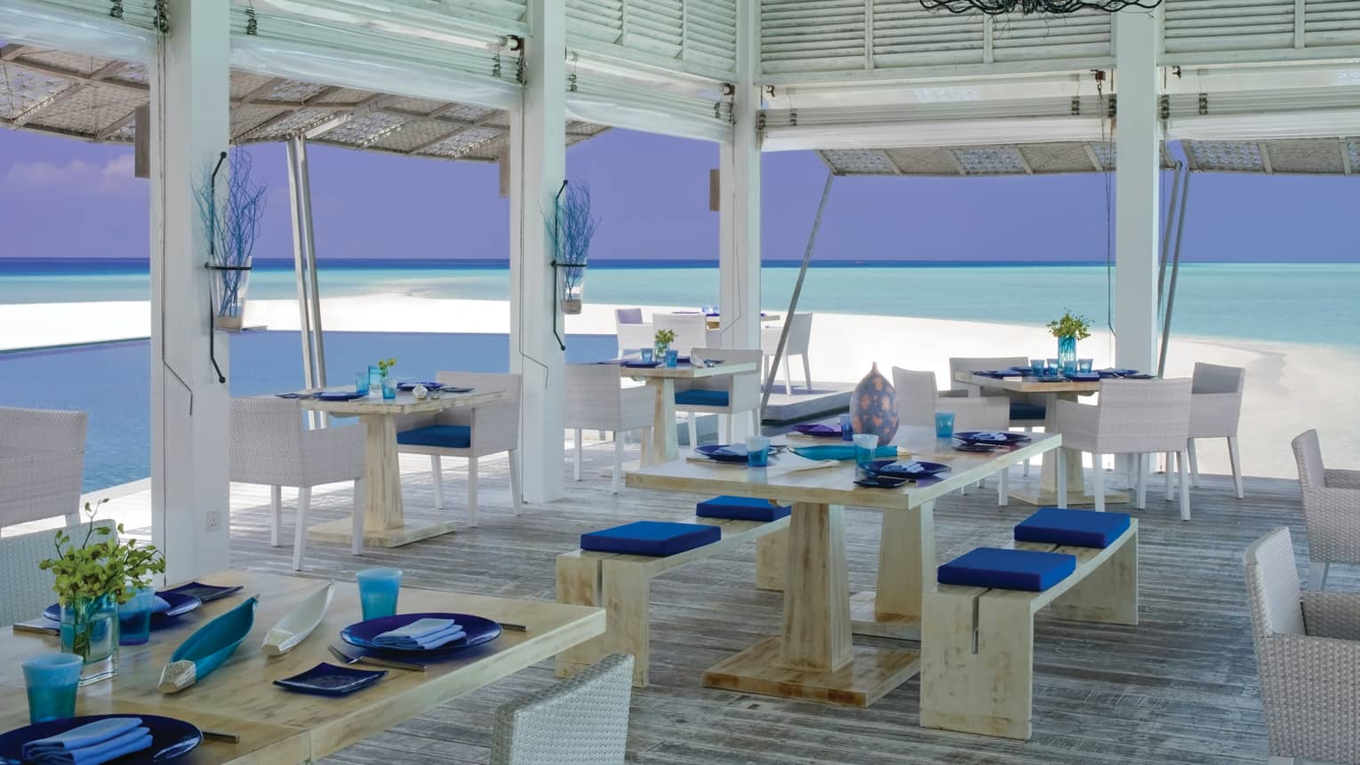 Blu patio, light wood tables, white wicker chairs, open-air walls with beach and ocean views