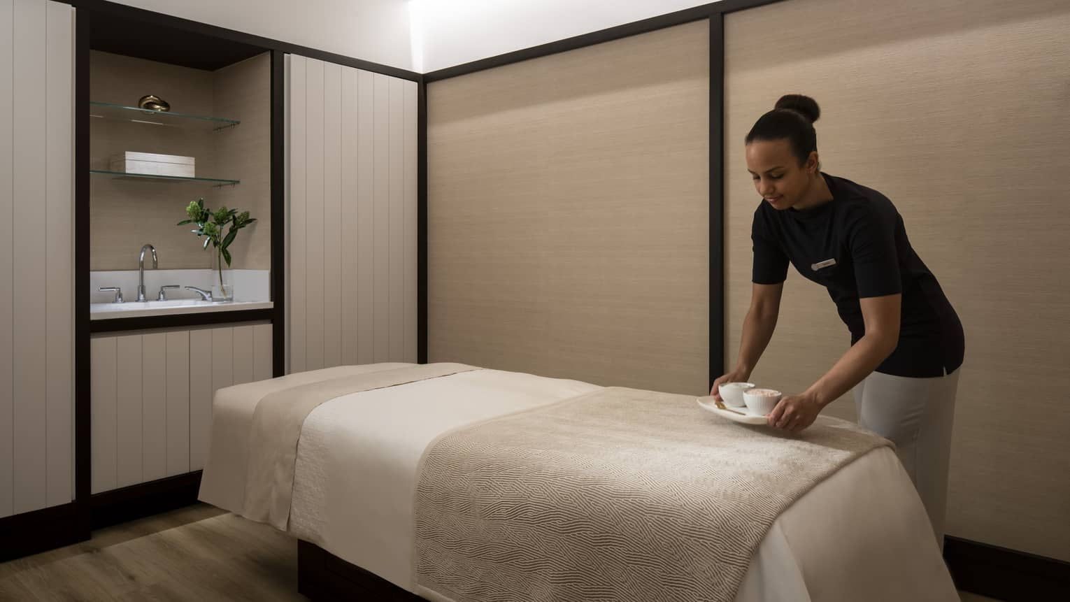 Spa staff places small dish on massage bed in couples suite