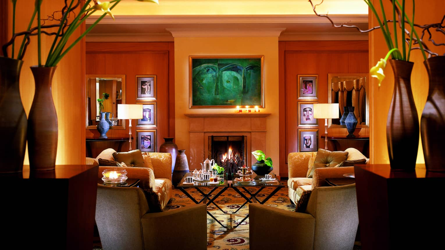 Afternoon tea on table by plush sofas and chairs, fireplace in Crown Room pre function area seating room