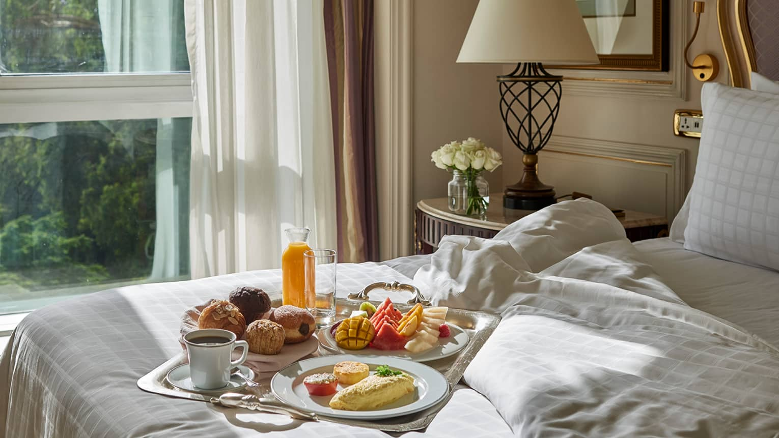 Breakfast tray with coffee, fresh tropical fruit, pastries, jug of orange juice on unmade bed