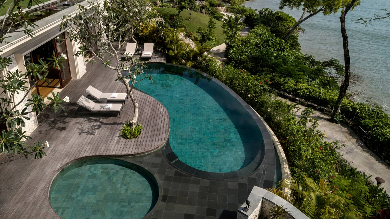 Looking down at Imperial Villa swimming pool and whirlpool on deck with white lounge chairs, garden path and ocean below