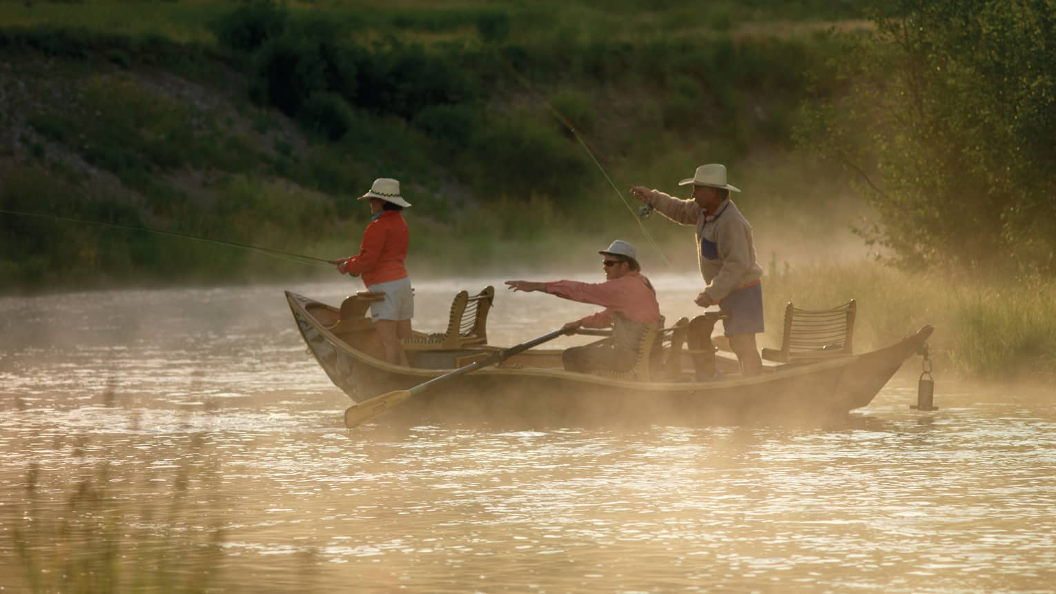 Mist rises from river over three people in fishing boat, one pointing to water