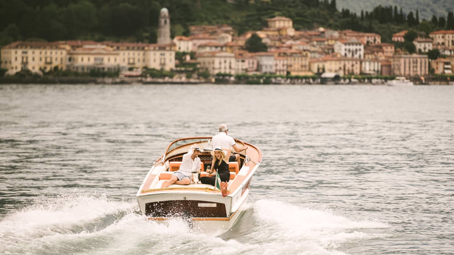 Couple laugh, drink Champagne on back of powerboat on Lake Como