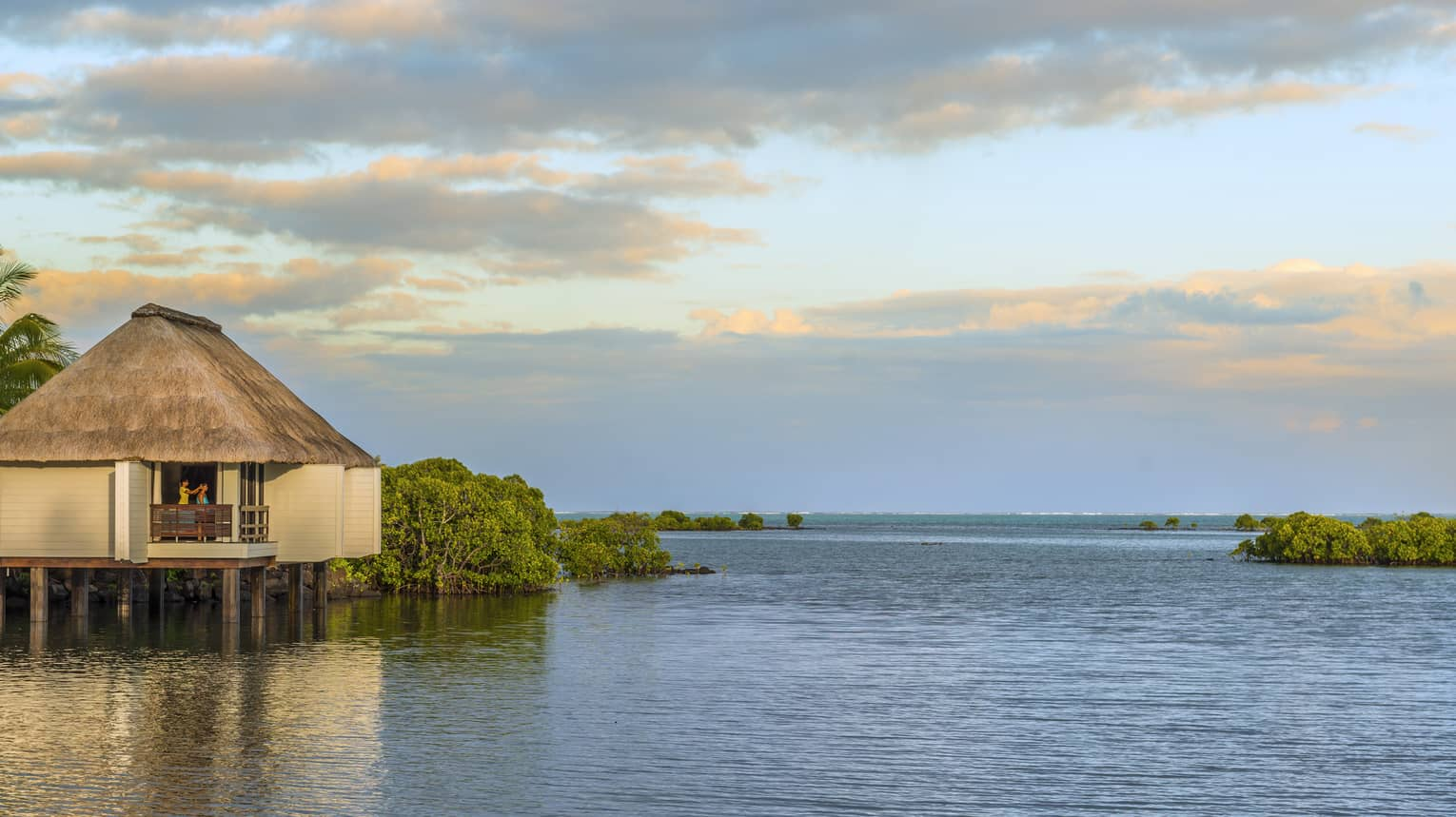 Overwater spa villa with thatched roof at sunrise