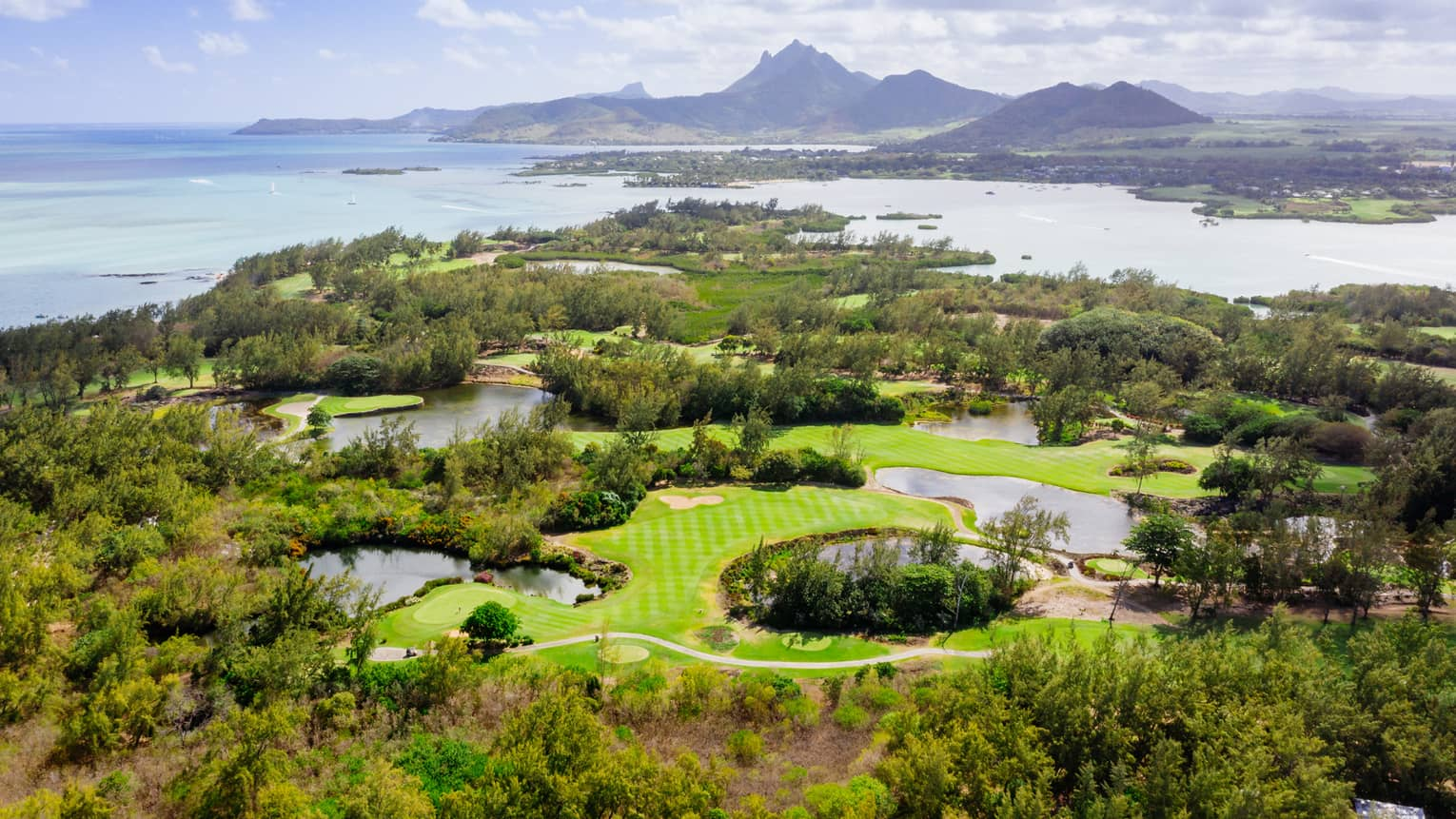 Aerial view of golf course with Indian Ocean and mountains in backdrop