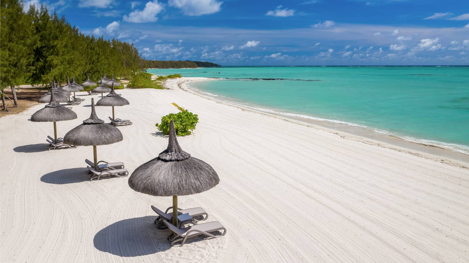 White sand beach with thatched umbrellas and lounge chairs and aqua ocean with blue sky above
