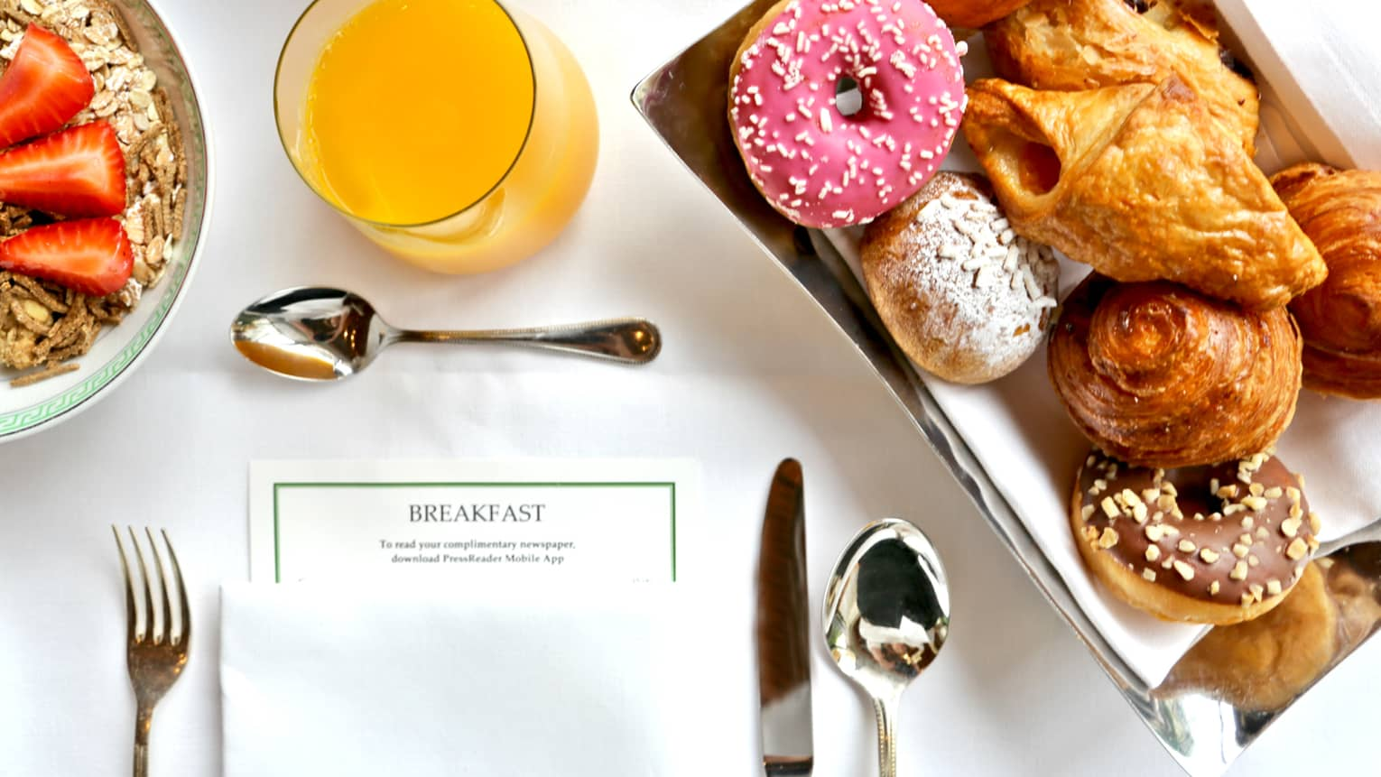Aerial view of in-room breakfast table with menu, tray with pastries, doughnut with pink icing, orange juice