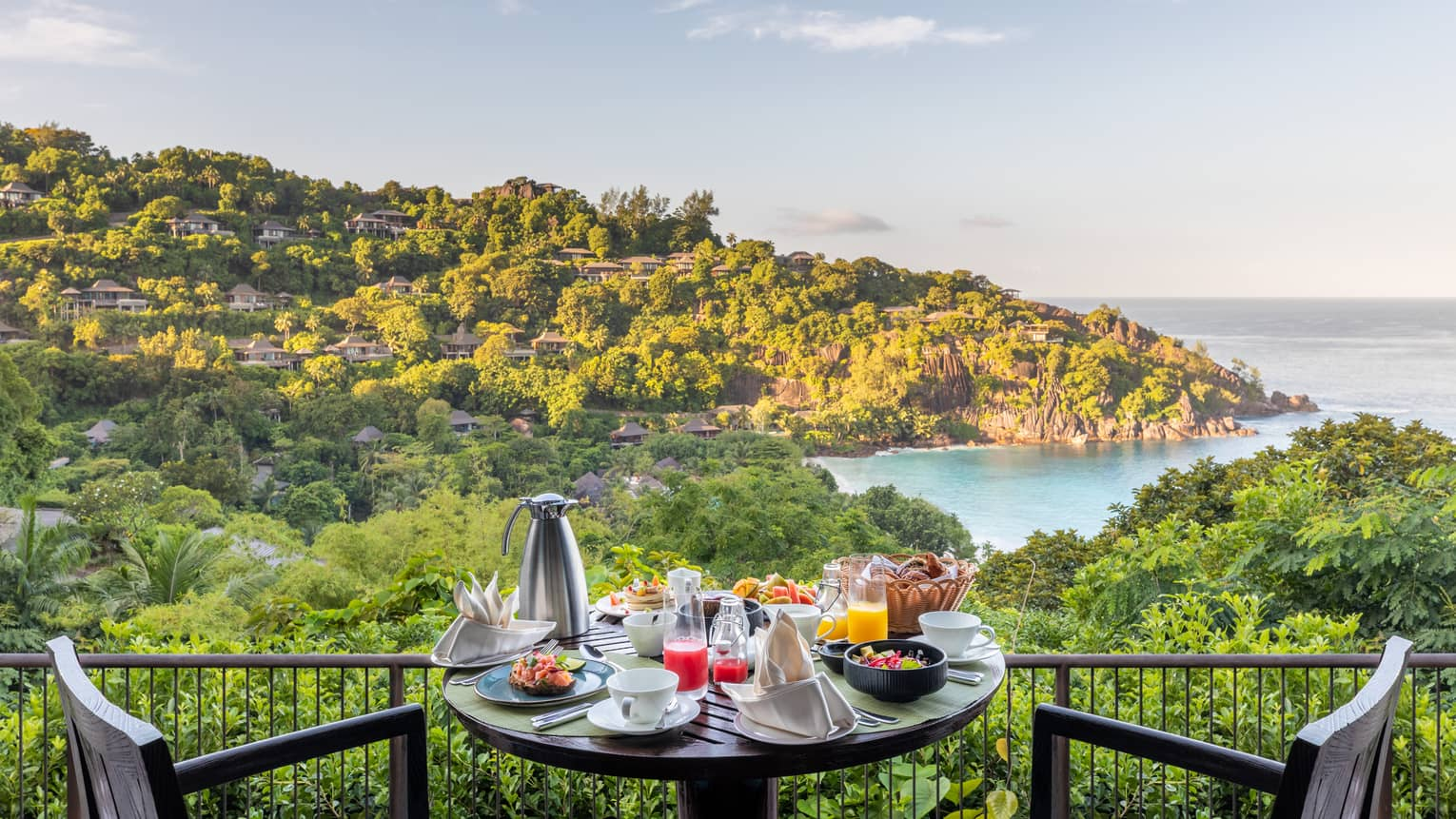 Bistro table and chairs with breakfast dishes and carafe, overlooking tropical hillsides and ocean