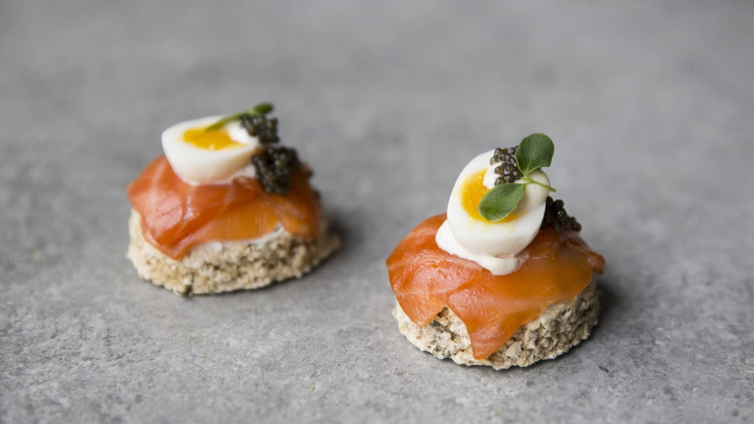 Toast rounds with smoked salmon, soft-cooked quail egg, caviar, microgreens garnish
