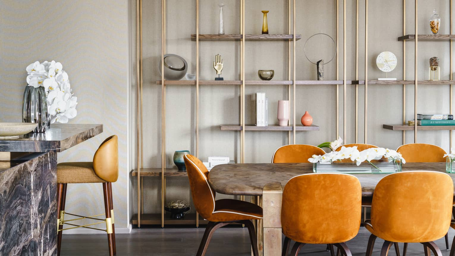 Dining table with orange velvet chairs, modern shelving on the wall, bar with high-top chair