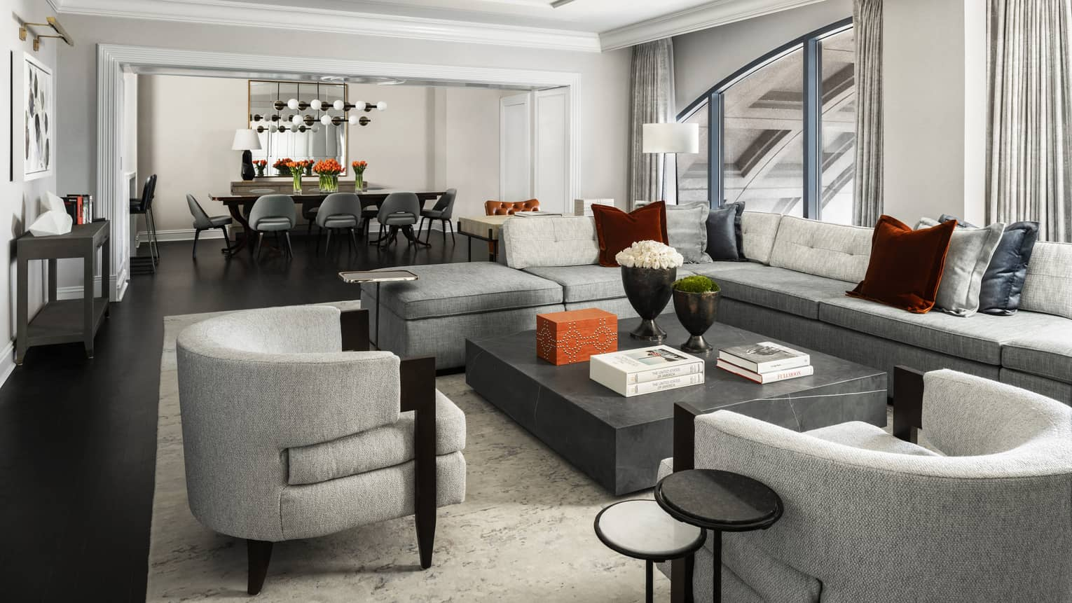 Presidential Suite large seating area with modern grey furniture, dining table