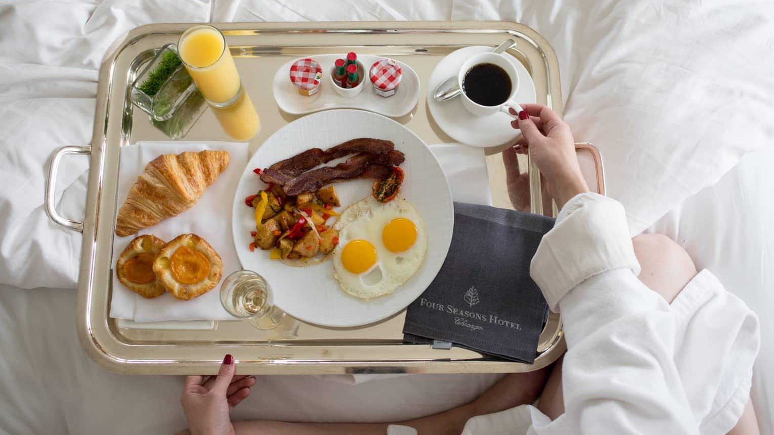 Aerial view of woman holding in-room dining tray with bacon, potatoes, fried eggs, pastries, juice, jam, Four Seasons menu