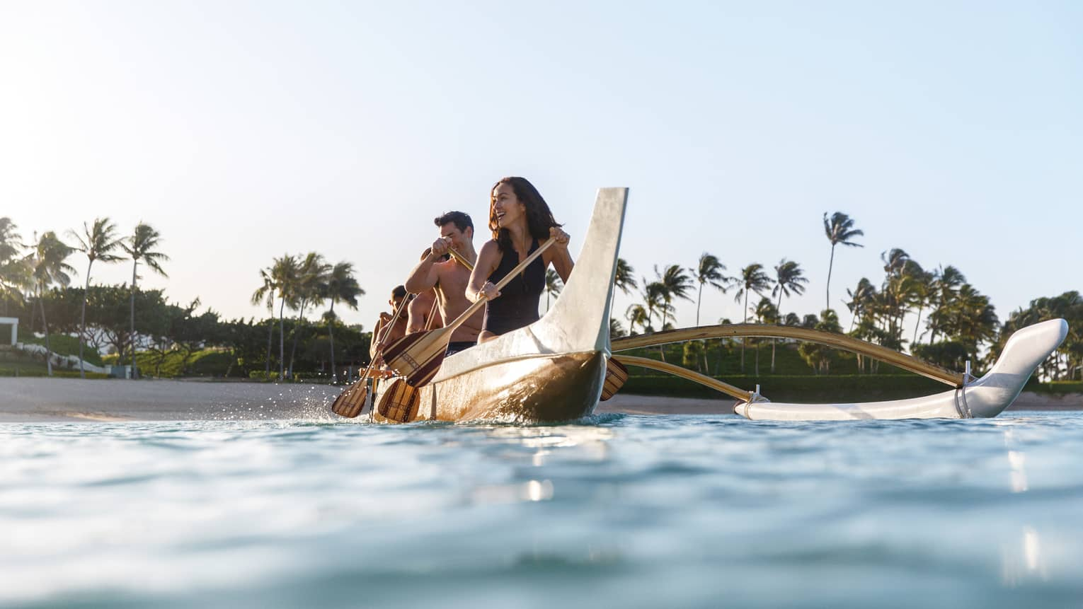 Group of friends paddle traditional wood outrigger canoe on ocean