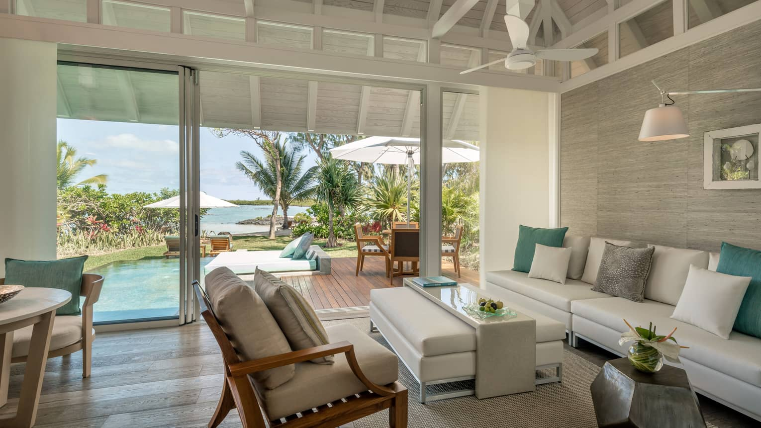 Sanctuary Beach Pool Villa with long white sofa, ottoman, chair, open glass wall to patio